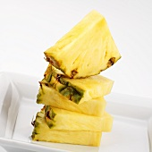 Pineapple quarters, stacked in white dish