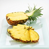 Half a pineapple and pineapple slices