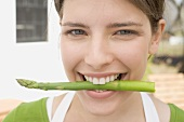 Young woman with an asparagus spear between her teeth