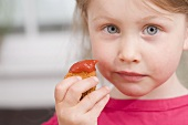 Little girl holding chicken nugget with ketchup