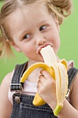 Little girl eating banana
