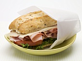 Ham, cheese, lettuce & tomato sandwich in greaseproof paper