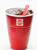 Cola with ice cubes and straw in plastic cup