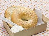 Sesame bagel with crème fraîche in a cardboard box