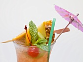 Cocktail with exotic fruit skewer and umbrella