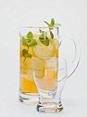 Iced tea with lemon slices and fresh mint in glass jug