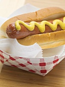 Hot dog with mustard in paper dish