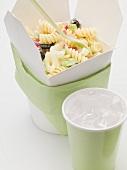 Fusilli mit Gemüse im Take-Out-Behälter, daneben Getränk
