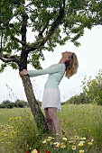 Woman clinging to a tree