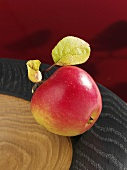 A McIntosh apple in a wooden bowl