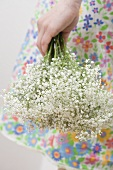 Woman in flowery dress holding gypsophila
