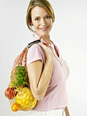 Woman holding string bag full of fruit and herbs