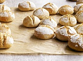 Organic bread rolls on baking parchment
