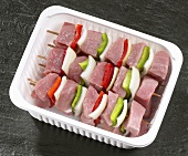 Meat kebabs in plastic container