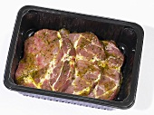 Marinated pork neck steaks in plastic container