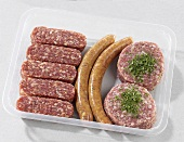Cevapcici, sausages and burgers in plastic container