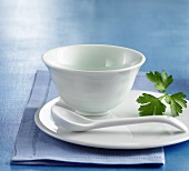White porcelain bowl on plate with spoon and parsley