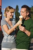 Cheerful couple with ice cream cones out of doors