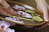Woman with her hand in bowl of water with orchids & lime slices
