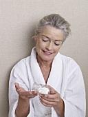 Ältere Frau im Bademantel hält Apothekerflasche mit Tabletten