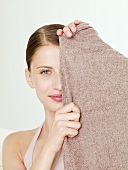 Woman holding woollen shawl in front of her face