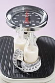 Two bottles of milk with tape measure on scales