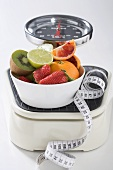 Bowl of fresh fruit and tape measure on scales