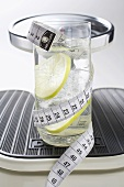 Glass of water with lime & tape measure on scales (close-up)