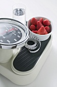 Strawberries, glass of water and tape measure on scales