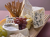 Cheese board with grapes and salted sticks