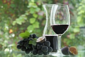 Red wine in glass and carafe, black grapes, figs