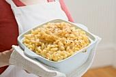 Frau hält Auflaufform mit Macaroni and Cheese