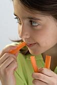 Kleines Mädchen isst Möhrensticks