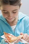 Little girl holding slice of pizza