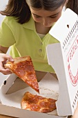 Little girl taking slice of pizza out of pizza box