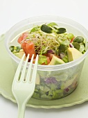 Avocado salad with sprouts in plastic container with fork