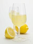 Two glasses of limoncello and fresh lemons