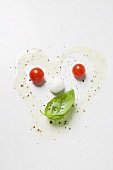 Tomatoes, mozzarella, basil, oil and spices forming a face