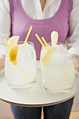 Woman holding tray of glasses filled with lemonade