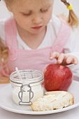 Little girl with apple, yoghurt and bread and butter