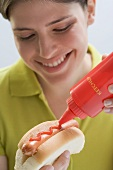 Young woman putting ketchup on hot dog