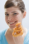 Young woman with deep-fried onion rings on index finger