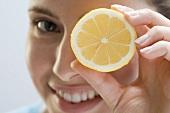 Junge Frau hält Zitrone vors Auge