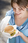 Young woman with cheeseburger out of doors