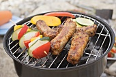 Ribs and vegetables on barbecue out of doors