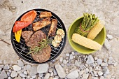 Meat & vegetables on barbecue, accompaniments in bowl