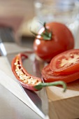 Tomatoes and half a chilli on chopping board with knife