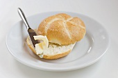 Bread roll with butter and knife on plate