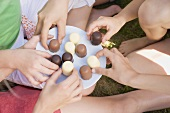 Children's hands reaching for chocolate-coated marshmallows