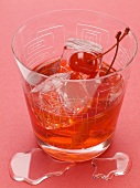 Manhattan with cocktail cherries and ice cubes